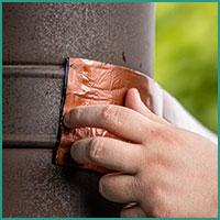 Abbildung Bitumenband Anwendund Ankleben an Fallrohr